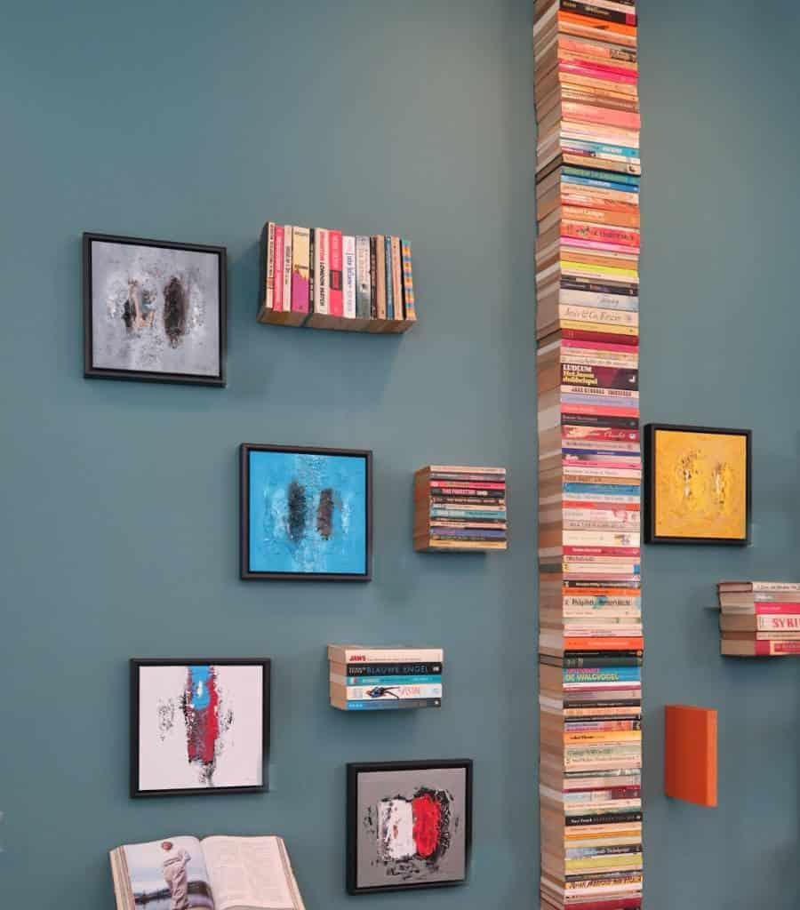 """Foto van boeken en schilderijn aan de muur van """"De Biebliotheek vergaderruimte"""
