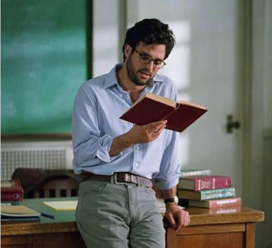 Man leest een boek terwijl hij op een tafel leunt.