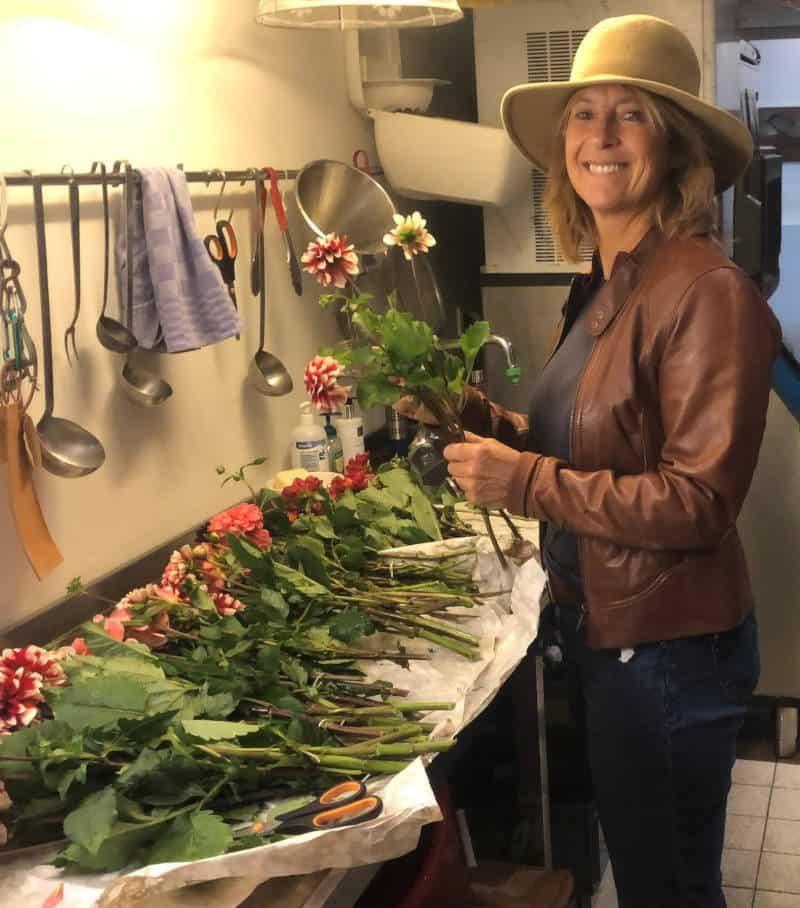 Juliëtte. Eigenaar Depot Noord is bloemen aan het samenstellen terwijl ze een hoed draagt